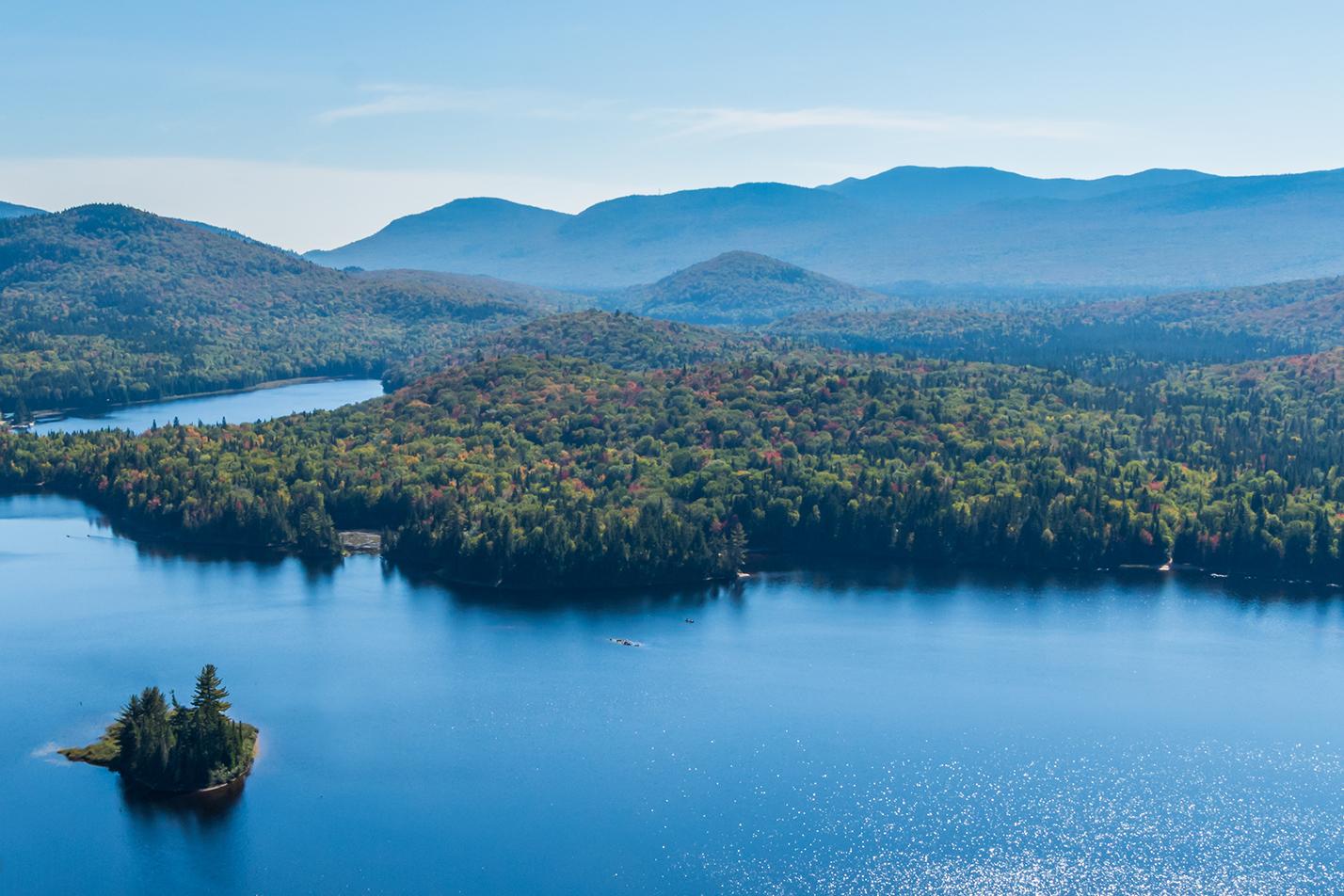 Vue aérienne d'un lac entouré de montagnes au Québec lors d'une journée d'automne.