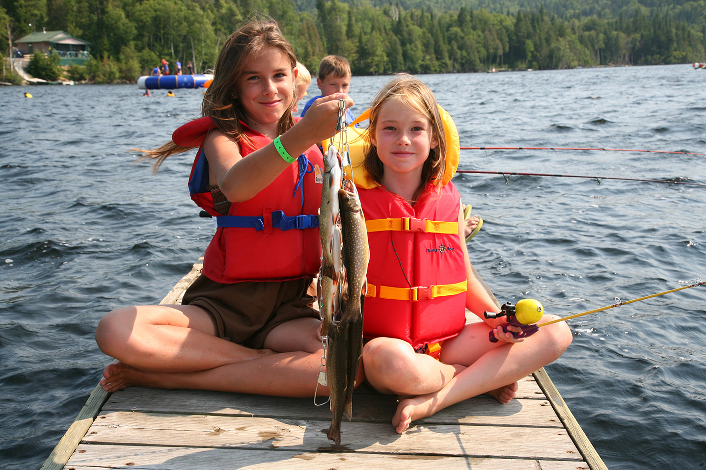 Deux petites filles avec leur veste de flottaison qui tiennent des poissons pêchés.