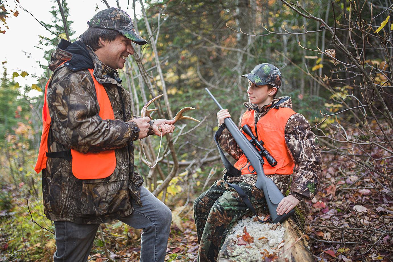 Adolescent qui tient son arme en compagnie d'un chasseur